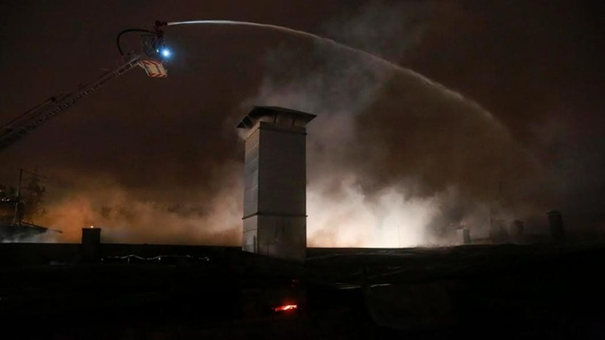 In this photo provided by Emergency Situations Ministry press service, a firefighter works from a platform high above a large blaze at a plastic warehouse in Moscow, Russia, Friday Sept. 23, 2016, with about 300 firefighters attending the incident.  Emergencies Ministry said eight firemen died while tackling the blaze which started Thursday.  ( Russian Emergency Ministry press service photo via AP) MANDATORY CREDIT