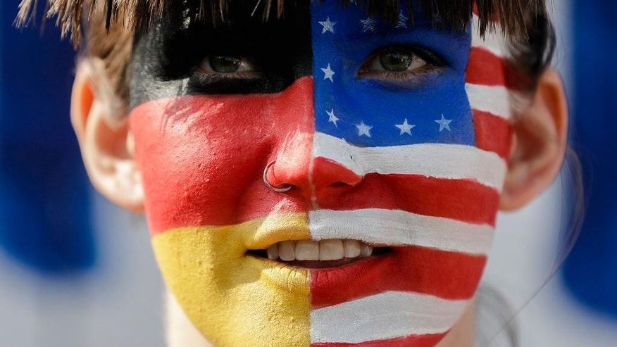 A woman with the face painted half and half with United States and German flag attends a protest where they are tearing down a so called 'Trump's wall of hate' as part of a demonstration against Republican presidential candidate Donald Trump at the Pariser Platz in Berlin, Germany, Friday, Sept. 23, 2016. (AP Photo/Markus Schreiber)