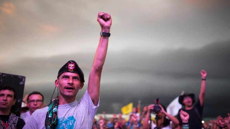 Rebels cheer during the closing event of the 10th conference held by the Revolutionary Armed Forces of Colombia, FARC, in Yari Plains, Colombia, Friday, Sept. 23, 2016. FARC leaders gave their unanimous support to a peace agreement reached last month with the government. (AP Photo/Ricardo Mazalan)