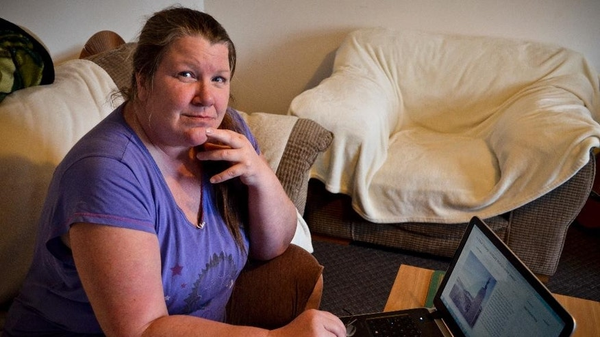 Faith Felton poses for a picture as she sits beside a laptop computer showing an online petition she created against recent talks between Britain and Argentina, at her home in Port Stanley, Falkland Islands, Thursday, Sep. 22, 2016. Some Falkland Islanders are protesting a recent thaw of relations between Argentina and Britain over the disputed islands. (AP Photo/Federica De Caria)