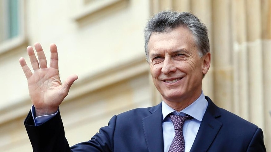 FILE - In this June 15, 2016 file photo, Argentina's President Mauricio Macri waves at journalists at the end of a welcoming ceremony at the Presidential Palace in Bogota, Colombia. Tensions have eased with the Falklands since Macri took office in December promising a less-confrontational stance. (AP Photo/Fernando Vergara, File)