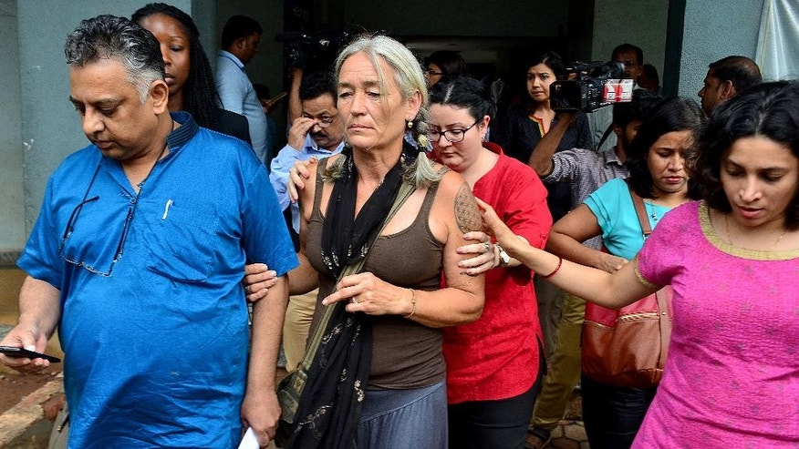 Fiona MacKeown, mother of Scarlett Keeling, leaves the court premises along with her lawyer Vikram Verma, left, in Panaji, India, Friday, Sept. 23, 2016. An Indian court has acquitted two suspects in the death of the 15-year-old British teenager Keeling whose body was found on a popular beach in western India in 2008. MacKeown said she was shocked by Friday's verdict and would challenge it in an appeals court. (AP Photo)