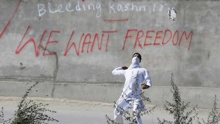 A Kashmiri Muslim protester throws stones at government forces in Srinagar, Indian controlled Kashmir, Friday, Sept. 23, 2016. Kashmir is witnessing the largest protests against Indian rule in recent years, sparked by the July 8 killing of a popular rebel commander by Indian soldiers. (AP Photo/Mukhtar Khan)