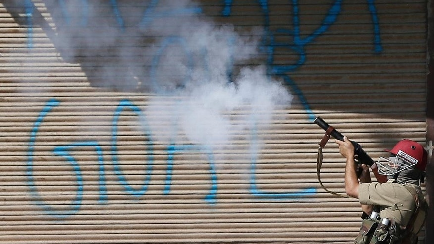"An Indian policeman fires a tear gas shell on Kashmiri protesters in front of a grafiti on shutters that reads ""Freedom our goal,"" in Srinagar, Indian controlled Kashmir, Friday, Sept. 23, 2016. Kashmir is witnessing the largest protests against Indian rule in recent years, sparked by the July 8 killing of a popular rebel commander by Indian soldiers. (AP Photo/Mukhtar Khan)"