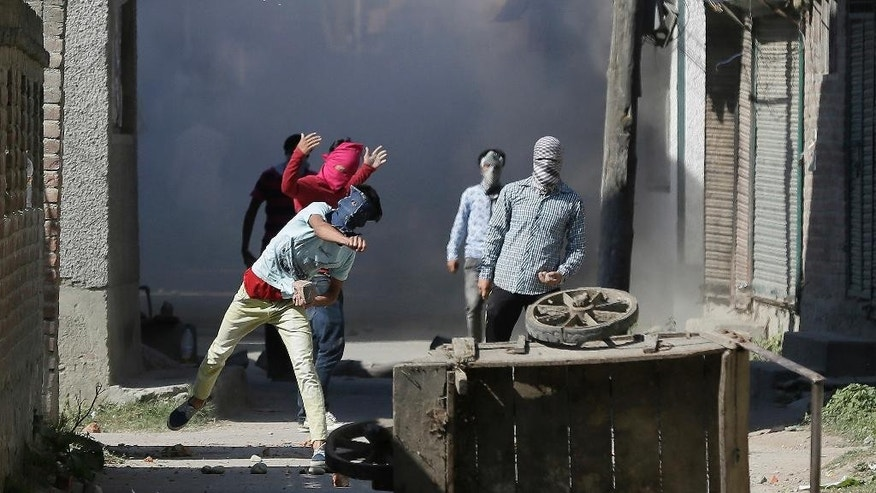 Kashmiri Muslim protesters throw stones at government forces in Srinagar, Indian controlled Kashmir, Friday, Sept. 23, 2016. Kashmir is witnessing the largest protests against Indian rule in recent years, sparked by the July 8 killing of a popular rebel commander by Indian soldiers. (AP Photo/Mukhtar Khan)