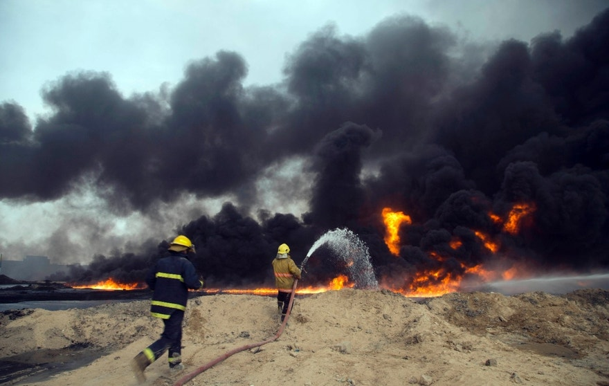 FILE - In this Aug. 31, 2016 file photo, Iraqi firefighters battle large fire at oil wells as they trying to prevent the flames from reaching the residential neighborhoods in Qayara, Iraq. A fire at one of Iraq's major oil fields could hinder military and humanitarian efforts as operations to recapture the Islamic State stronghold of Mosul get under way. Black smoke continues to billow into the air from the Qayara oil field, damaged by IS militants last month as they fled the town. There are slow-going Iraqi efforts to contain the fires, but smoke and toxic fumes continue to pollute the air in the area.  (AP Photo, File)