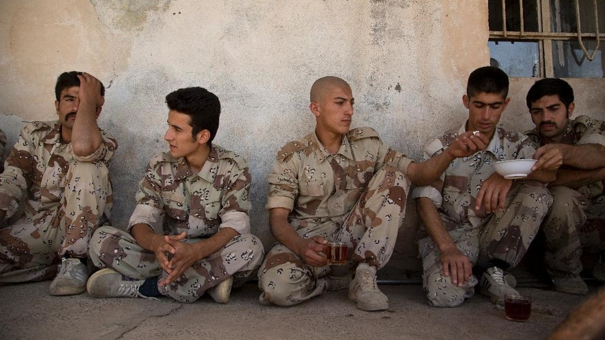 """In this Wednesday, Sept. 21, 2016 photo, new recruits of the Democratic Party of Iranian Kurdistan take a tea break after training at their base in Koya, northern Iraq. The main Kurdish opposition group in Iran will keep up its guerrilla campaign against security forces """"to protect and defend"""" Kurds living there. That's according to the deputy leader of the Democratic Party of Iranian Kurdistan. He calls the fight necessary after the Islamic Republic's nuclear deal with world powers.(AP Photo/Maya Alleruzzo)"""