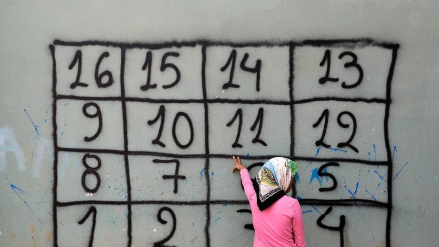 "An Afghan girl counts in Greek the numbers on the wall during a lesson by a non governmental organization at a refugee camp in the western Athens' suburb of Schisto, on Thursday, Sept. 22, 2016. Most of the roughly 60,000 refugees and other migrants stranded in Greece are living in ""appalling conditions"" and face ""immense and avoidable suffering,"" rights group Amnesty International said in a report Thursday slamming Europe's response to the refugee crisis. (AP Photo/Thanassis Stavrakis)"
