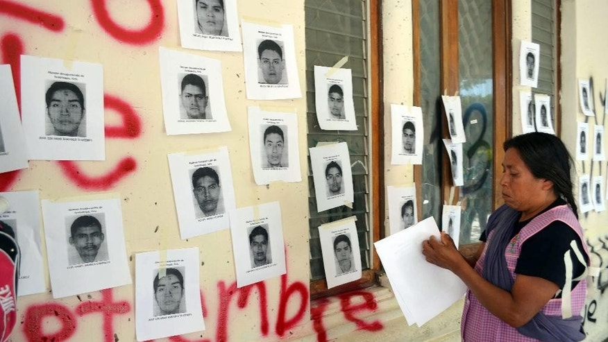 Genoveva Sanchez, mother of Israel Caballero Sanchez, one of the 43 missing students, pastes images of the missing students on the walls of the main Guerrero state courthouse in the city of Chilpancingo, Mexico, Friday, Sept. 23, 2016. She and other protesters are demanding the court make public a video that is part of the evidence in the case of the missing students. Also, Mexico's Attorney General's Office says it wants to perform a new forensic examination of a garbage dump where it has maintained that the missing students were incinerated by a drug gang two years ago. (AP Photo/Alejandrino Gonzalez)