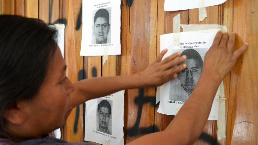 Genoveva Sanchez, mother of Israel Caballero Sanchez, one of the 43 missing students, pastes an image of her son on the walls of the main Guerrero state courthouse in the city of Chilpancingo, Mexico, Friday, Sept. 23, 2016. She and other protesters are demanding the court make public a video that is part of the evidence in the case of the missing students. Also, Mexico's Attorney General's Office says it wants to perform a new forensic examination of a garbage dump where it has maintained that the missing students were incinerated by a drug gang two years ago. (AP Photo/Alejandrino Gonzalez)