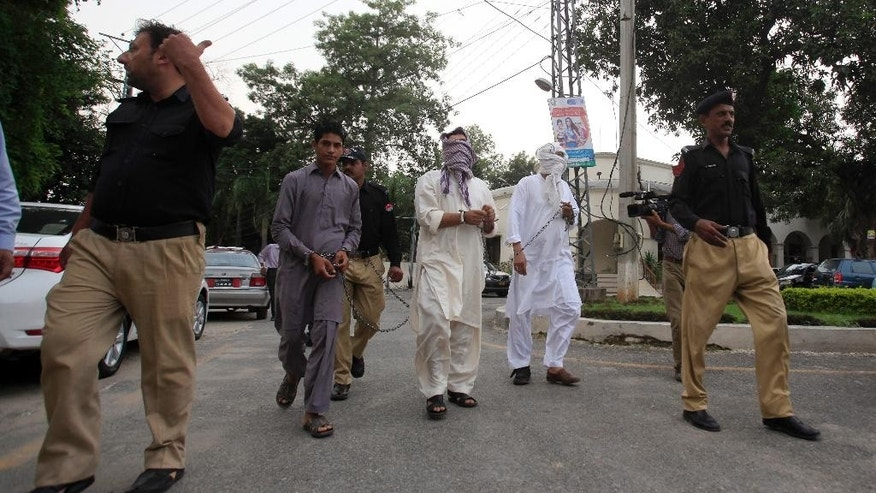 Pakistani police officers escort father Muhammad Shahid, second right, and ex-husband Muhammad Shakeel, third right, of slain British-Pakistani woman Samia Shahid to a court in Jhelum in eastern Pakistan, Friday, Sept. 23, 2016. Pakistani police have submitted initial charges to a court against the two men for holding their trial for killing her, court officials and a defense lawyer said. (AP Photo/Anjum Naveed)