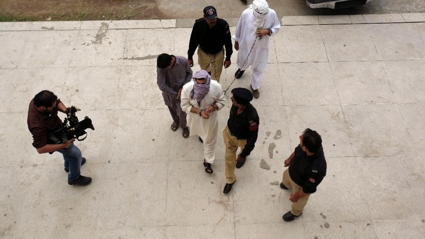Pakistani police officers escort ex-husband Muhammad Shakeel, bottom center, and father Muhammad Shahid, top right, of slain British-Pakistani woman Samia Shahid to a court in Jhelum, in eastern Pakistan, Friday, Sept. 23, 2016. Pakistani police have submitted initial charges to a court against the two men for holding their trial for killing her, court officials and a defense lawyer said. (AP Photo/Anjum Naveed)