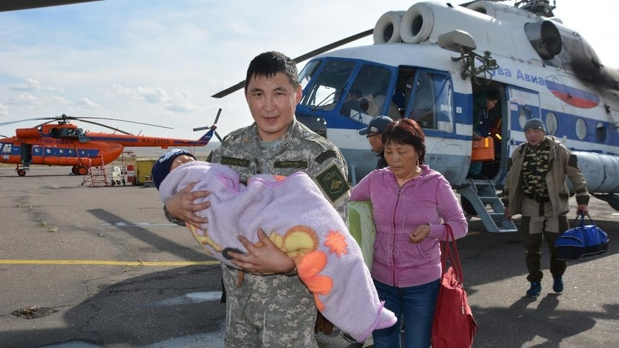 In this photo dated Wednesday, Sept. 21, 2016, provided by the Tuva Emergency Ministry Situations press service, an unidentified special force soldier carries a 3-year old boy rescued after going missing for three days in an undisclosed location in the Russian Siberian region of Tuva. The boy, who was under care of his grandmother, reportedly vanished in the woods after having followed a puppy. (Tuva Emergency Situations Ministry press service photo via AP) MANDATORY CREDIT