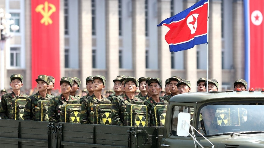 In this Saturday, July 27, 2013, file photo, North Korean soldiers turn and look towards leader Kim Jong Un as they carry packs marked with the nuclear symbol during a parade marking the 60th anniversary of the Korean War armistice in Pyongyang, North Korea.
