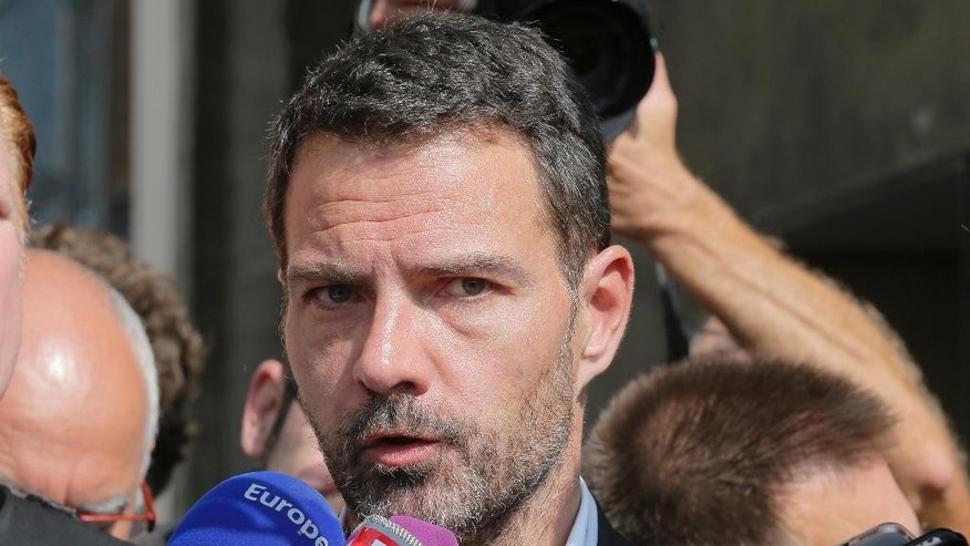 Former trader Jerome Kerviel speaks to the media at the Versailles appeal court, west of Paris, Friday, Sept. 23, 2016. A French court has cut the civil damages owed by former trader Jerome Kerviel from 4.9 billion euros ($5.5 billion) to 1 million euros ($1.1 million). (AP Photo/Michel Euler)