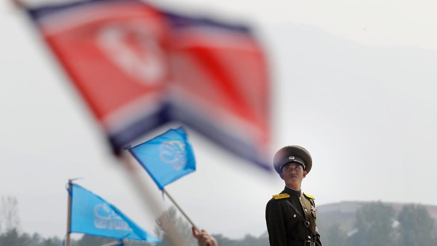 A North Korean military soldier stands guard as North Koreans wave flags and cheer during an aerial display on Saturday, Sept. 24, 2016, in Wonsan, North Korea. North Korea on Saturday opened an air festival featuring sky diving, demonstrations by its air force and lots of beer to promote a newly renovated and upgraded commercial airport in the coastal city of Wonsan that it hopes will draw for foreign tourists. (AP Photo/Wong Maye-E)