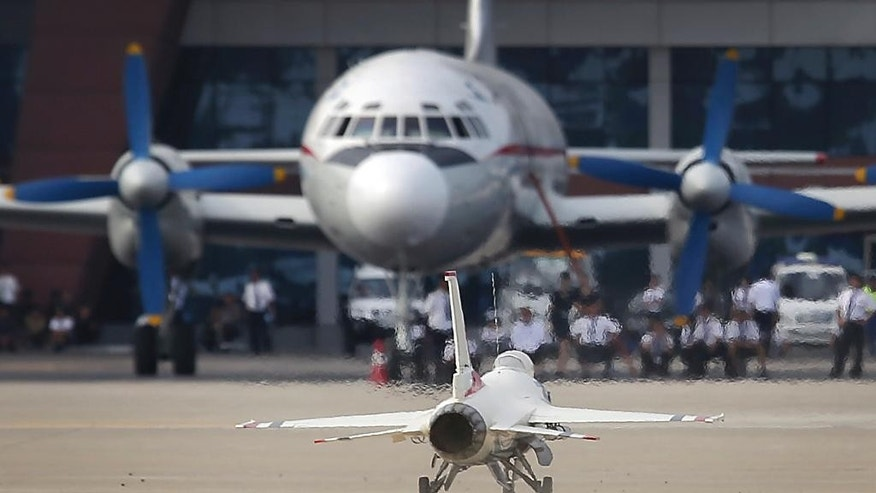 A remote-controlled F-16 fighter jet lands in front of an Air Koryo commercial airplane at the Kalma Airport after a flight demonstration on Sunday, Sept. 25, 2016, in Wonsan, North Korea. Thousands of Koreans and hundreds of foreign tourists and journalists invited to Wonsan, for the Wonsan International Friendship Air Festival, were given a glimpse of North Korea's own Air Force fighters, remote-controlled scale mock-up planes including an F-16 fighter jet, and demonstrations of military parachuting, with the first two skydivers descending with huge North Korean and ruling party flags. (AP Photo/Wong Maye-E)