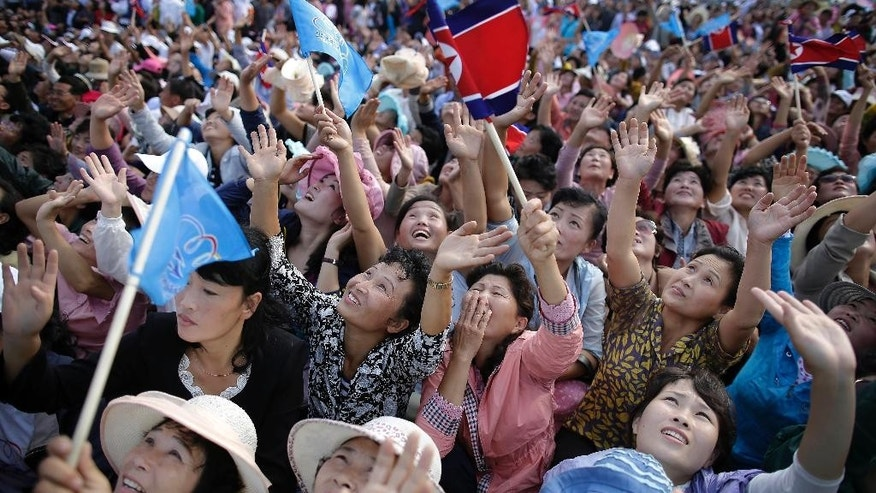 North Korean men and women wave flags and cheer as they watch a military parachuting demonstration at the Kalma Airport on Sunday, Sept. 25, 2016, in Wonsan, North Korea. Thousands of Koreans and hundreds of foreign tourists and journalists invited to Wonsan, a port city, for the Wonsan International Friendship Air Festival, were given a glimpse of North Korea's own Air Force fighters, remote-controlled scale mock-up planes including an F-16 fighter jet, and demonstrations of military parachuting, with the first two skydivers descending with huge North Korean and ruling party flags. (AP Photo/Wong Maye-E)