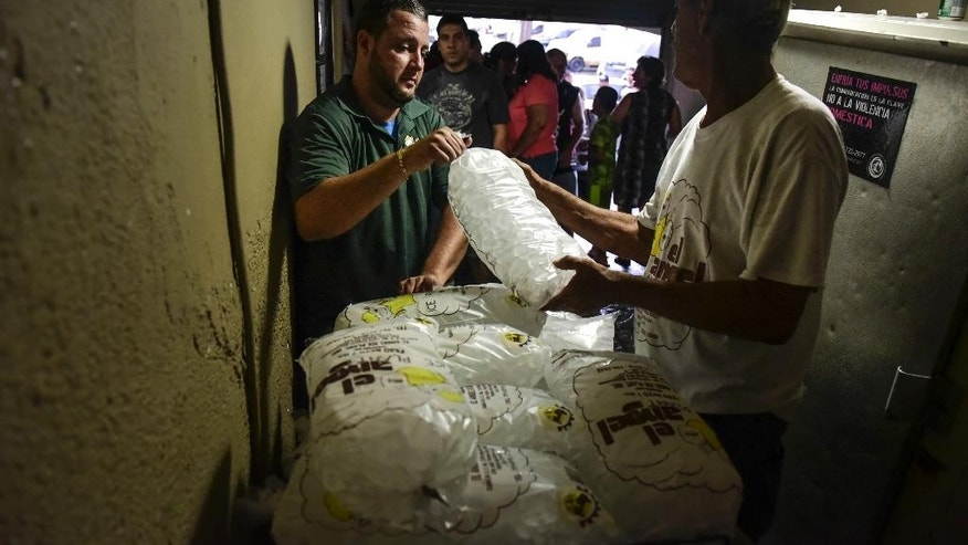 People buy ice during a massive blackout in San Juan, Puerto Rico, Thursday, September 22, 2016. Puerto Ricans faced another night of darkness Thursday as crews slowly restored electricity a day after a fire at a power plant caused the aging utility grid to fail and blacked out the entire island. (AP Photo/Carlos Giusti)