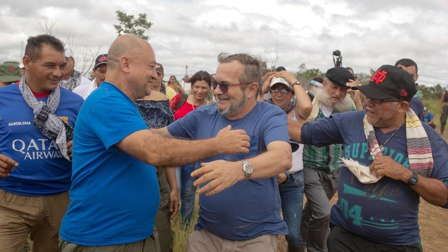 Rodrigo Londono, also known as Timochenko, the top leader of the Revolutionary Armed Forces of Colombia, FARC, second from right embraces rebel leader Carlos Alonso Lozada, before boarding a helicopter in Yari Plains, southern Colombia, Saturday, Sept. 24, 2016. Londono and Colombia's President Juan Manuel Santos are expected to sign a peace accord to end a more than five decades civil conflict in the Caribbean city of Cartagena on Sept. 26. (AP Photo/Ricardo Mazalan)