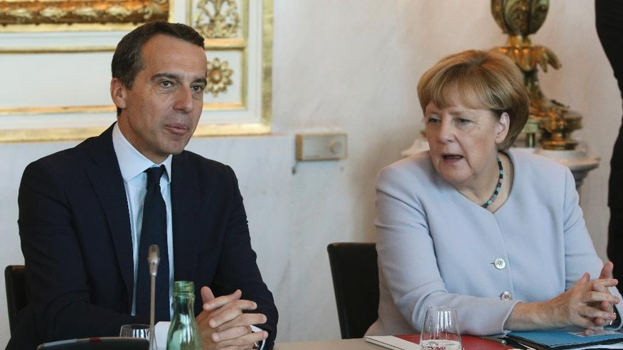 Austrian Chancellor Christian Kern, left, talks with German Chancellor Angela Merkel in Vienna, Austria, Saturday, Sept. 24, 2016, at the beginning of a meeting of Kern and his German and West Balkans counterparts on strategies to deal with Europe's migrant crisis. (AP Photo/Ronald Zak)