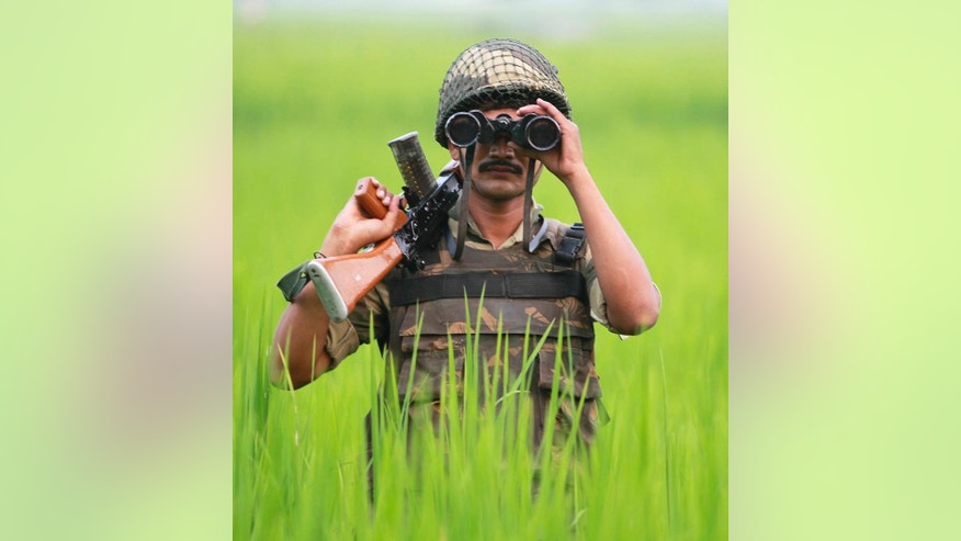 An Indian Border Security Force soldier looks at the Pakistan side of the border through a binocular at Ranbir Singh Pura, about 35 kilometers (22 miles) from Jammu, India, Saturday, Sept. 24, 2016. Prime Minister Narendra Modi said in a speech Saturday that in the last four months, Indian security forces have killed more than 100 terrorists who crossed over the cease-fire line in Kashmir from Pakistani territory. (AP Photo/Channi Anand)
