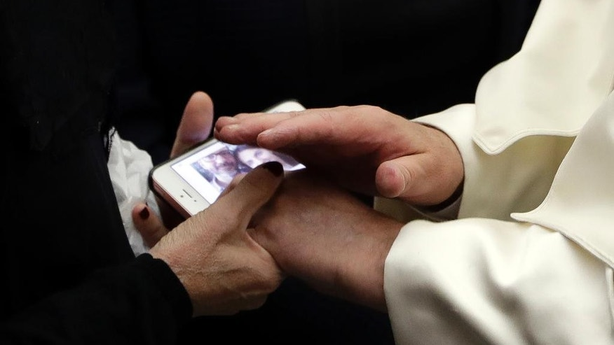 Pope Francis blesses a photo he is shown on a smartphone during a meeting with relatives of Nice's attack victims during a special audience in the Pape Paul IV hall, at the Vatican, Saturday, Sept. 24, 2016. (AP Photo/Andrew Medichini)