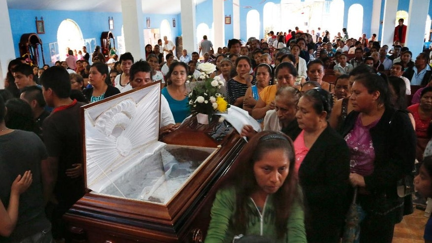 This Sept. 21, 2016 photo shows people paying their last respects to slain Rev. Jose Alfredo Suarez de la Cruz, who was found bound and shot to death alongside another priest, inside Our Lady of Asuncion Church in Paso Blanco, Veracruz state, Mexico, his hometown. In this eastern oil town already weary of rising gangland violence and extortion, the abduction and murder of two priests this week sank many residents only deeper into despair. (AP Photo/Marco Ugarte)