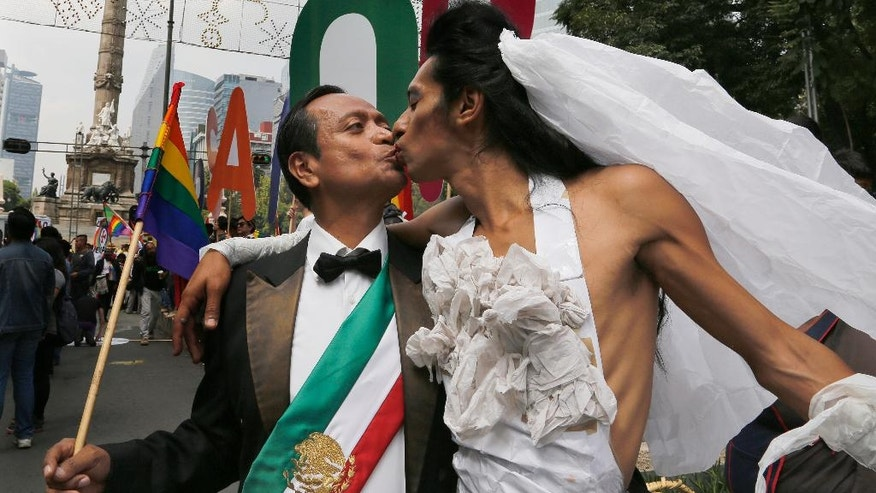 Men kiss as they arrive at the Angel of Independence monument, after  in Mexico City, Saturday, Sept. 24, 2016. Dueling marches, in support and against Mexican President Enrique Pena Nieto's push to legalize same-sex marriage, gathered at the Angel of Independence monument. The two sides were kept apart Saturday by hundreds of police and barriers erected around the city's iconic monument. (AP Photo/Marco Ugarte)