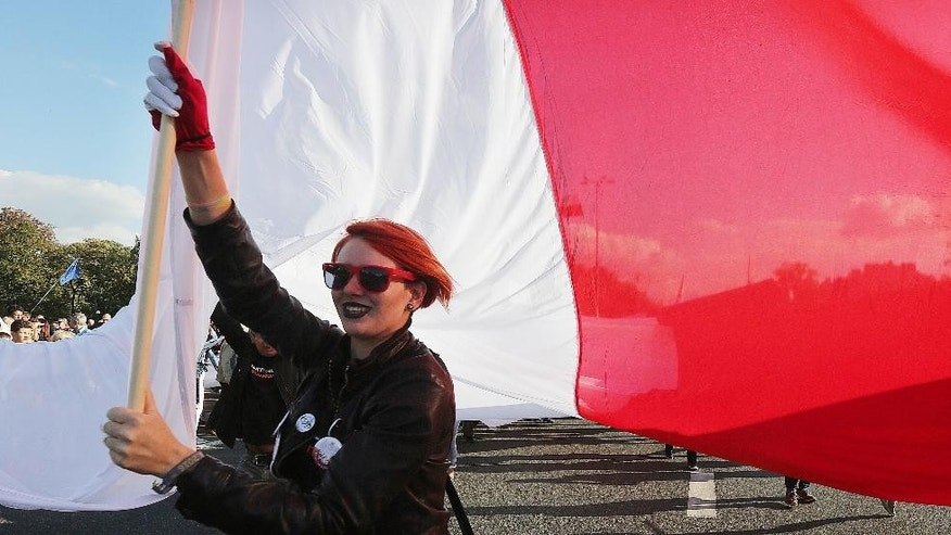 A young protestor holds a giant Polish flag during a demonstration in Warsaw, Poland, Saturday, Sept. 24, 2016, in the latest protest against the policies of the conservative government that critics say are dividing the nation. Protesters came from many corners of Poland for the protest organized by the Committee for the Defense of Democracy, or KOD. The group has organized regular protests against the 10-month-old Law and Justice government. (AP Photo/Czarek Sokolowski)