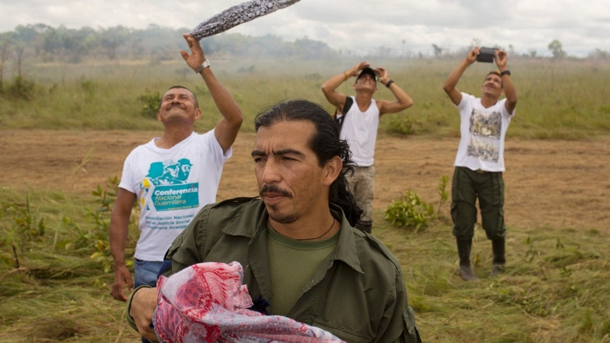 Rebels wave as a helicopter transporting FARC leaders takes off from Yari Plains, Colombia, Sept. 24, 2016.