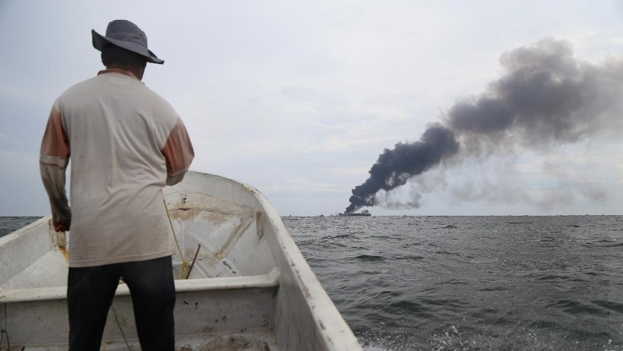 A man on a small boat watches as smoke billows from the tanker Burgos after a fire broke out aboard the ship about seven nautical miles off the coast of the port city of Boca del Rio, Mexico, Saturday, Sept. 24, 2016. The tanker was carrying about 168,000 barrels of gasoline and diesel fuel. Mexico's Navy rescued 31 crew members and no injuries were reported. There were no immediate reports of fuel spills and the cause of the fire was unknown. (AP Photo/Ilse Huesca)