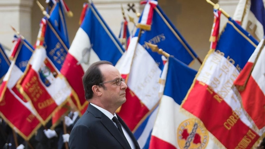 French president Francois Hollande stands to attention during a ceremony in which he acknowledged the state's responsibility in abandoning Algerians who fought alongside French colonial forces in Algeria's war for independence, in Paris, Sunday, Sept. 25, 2016. Tens of thousands of the fighters, known as harkis, were killed after the French withdrawal, and those who made it to France were placed in camps. (Ian Langsdon/Pool Photo via AP)