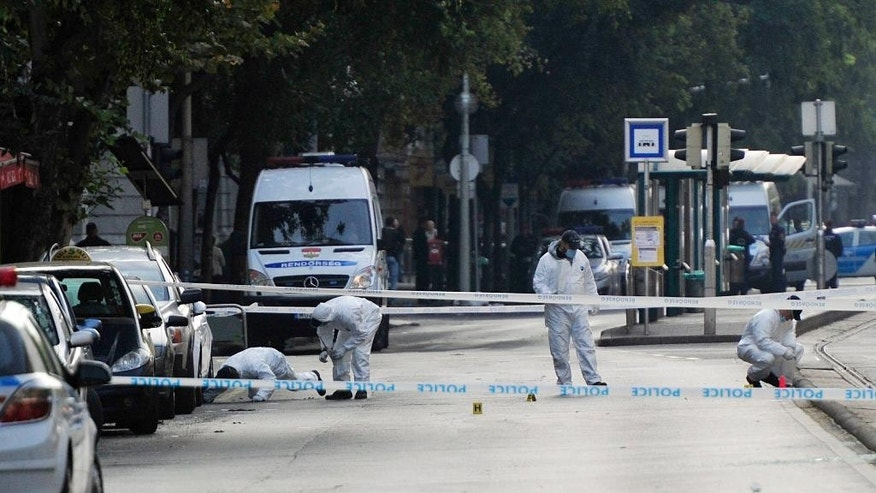 Police forensic experts examine the scene in central Budapest, Hungary, Sunday, Sept. 25, 2016, after an explosion of yet unknown origin occured in a shop late Saturday night. According to an expert apparently a home made bomb went off in front of the shop. The explosion injured two patrolling policemen. (Peter Lakatos/MTI via AP)