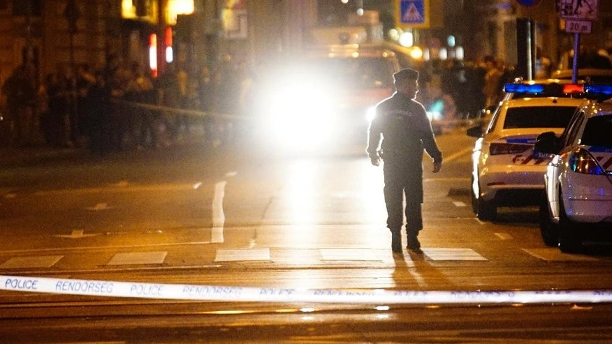 Police officers cordon off the area of the scene in central Budapest, Hungary, early Sunday, Sept. 25, 2016, after an explosion of yet unknown origin occured in a shop late Saturday nigh injured two patrolling policemen. (Zoltan Balogh/MTI via AP)