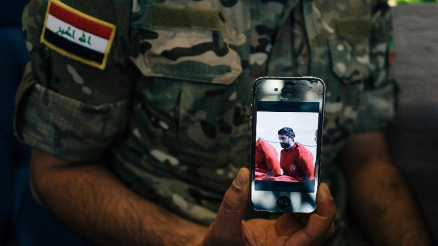In this Aug. 10, 2016 photo, Iraqi Army Cpl. Saif holds a phone displaying a screenshot from a video released by the Islamic State group that shows his brother, in Irbil, Iraq. He claims the video showed his brother's execution. The disparate groups that make up Iraq's security forces are converging on the city of Mosul, lining up for a battle on the historic plains of northern Iraq that is likely to be decisive in the war against the Islamic State group. (AP Photo/Alice Martins)