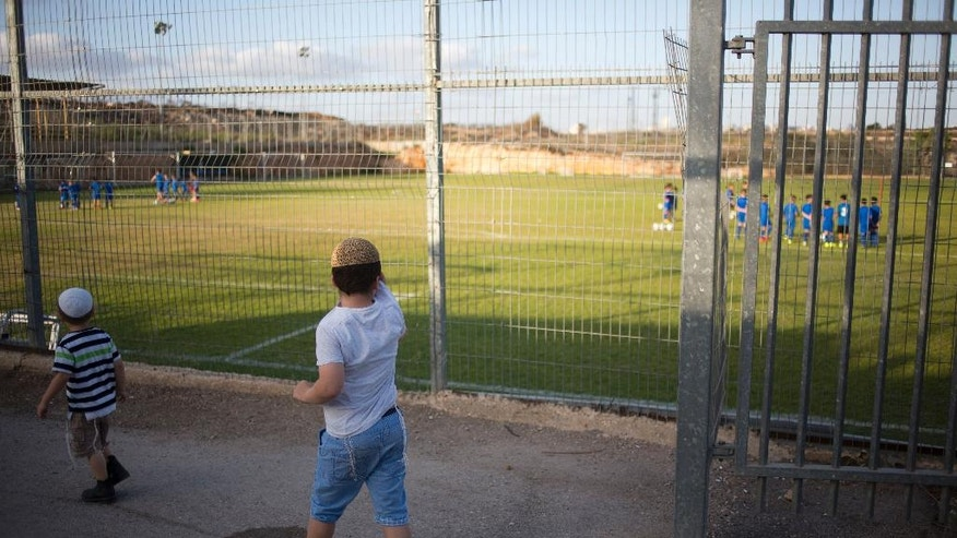 In this Thursday, Sept. 22, 2016 photo, Jewish settler children watch a soccer training session of the Beitar Shabi Givat Zeev  soccerclub in the West Bank Jewish settlement of Givat Zeev, near Jerusalem. Soccer clubs based in Israeli West Bank settlements are at the center of a showdown between Israelis and Palestinians that is set to draw soccer's global governing body FIFA into a tense dispute over Mideast politics. The Palestinians are pushing FIFA to declare the teams illegal at a meeting in Switzerland next month. (AP Photo/Ariel Schalit)