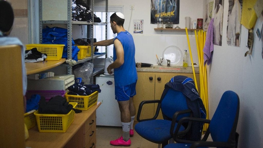 In this Thursday, Sept. 22, 2016 photo, Beitar Shabi Givat Zeev soccer club player, Avihay Salis, makes coffee ahead of training at the club's changing room in the West Bank Jewish settlement of Givat Zeev, near Jerusalem. Soccer clubs based in Israeli West Bank settlements are at the center of a showdown between Israelis and Palestinians that is set to draw soccer's global governing body FIFA into a tense dispute over Mideast politics. The Palestinians are pushing FIFA to declare the teams illegal at a meeting in Switzerland next month. (AP Photo/Ariel Schalit)