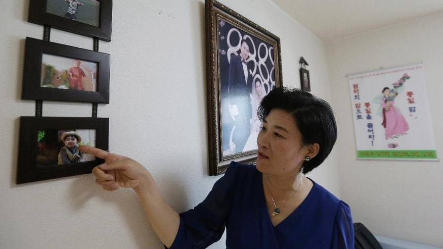 In this Sept. 4, 2016 photo, North Korean defector Kim Jungah points to a photo of his son left behind in China, during an interview at her house in Gunpo, South Korea. Kim Jungah, a North Korean living in the South who was separated from her child in China, will lead three other defectors on a trip to the United States in October to seek help from U.S. and United Nations officials to get their children back. North Korean women trafficked into China and sold as wives to farmers are often separated from their children when they flee to the South. (AP Photo/Ahn Young-joon)