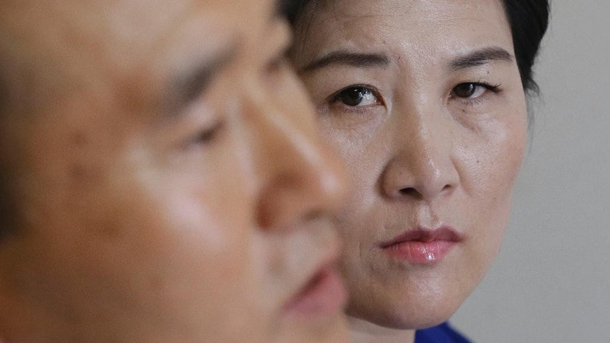 In this Sept. 4, 2016 photo, North Korean defector Kim Jungah, right, watches her husband Kim Jong Phil speak during an interview at their house in Gunpo, South Korea. Kim Jungah, a North Korean living in the South who was separated from her child in China, will lead three other defectors on a trip to the United States in October to seek help from U.S. and United Nations officials to get their children back. North Korean women trafficked into China and sold as wives to farmers are often separated from their children when they flee to the South. (AP Photo/Ahn Young-joon)