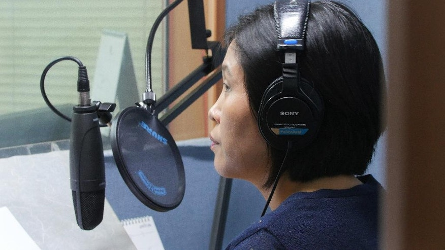 In this Aug. 25, 2016 photo, North Korean defector Park Kyung-hwa who works for a Seoul-based shortwave radio station targeting audience in North Korea, demonstrates how she records her broadcast at a church in Seoul, South Korea. Park, who fled the North in 2000 before being sold to a Chinese man, said she saw brokers grope other trafficked women many times. She said brokers kicked and beat her with wooden clubs for about 20 minutes when her first attempt to escape failed. (AP Photo/Jungho Choi)