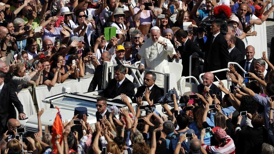 Pope Francis waves to cheering faithful as he is driven through the crowd after celebrating a Jubilee Mass for catechists, at the Vatican, Sunday, Sept. 25, 2016. (AP Photo/Andrew Medichini)