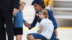 Kate, the Duchess of Cambridge, holds her daughter Princess Charlotte as she speaks to her son Prince George as she and her husband Britain's Prince William, the Duke of Cambridge, arrive in Victoria, British Columbia, on Saturday, Sept. 24, 2016. (Darryl Dyck/The Canadian Press via AP)