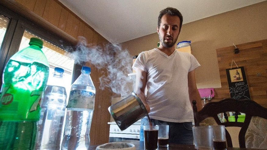 HOLD FOR RELEASE IN ADVANCE OF SEPT. 26 FOR USE WITH STORY BY HAMZA HENDAWI -In this photo taken Monday, Aug. 15, 2016, Mohammed al-Haj makes coffee in his home in Saarbruecken, Germany. Al-Haj, a native of the city of Aleppo, Syria's one-time economic capital that now lies in ruins, came to the western German state of Saarland in September 2015 to benefit from its swift processing of migrants. (AP Photo/Jens Meyer)