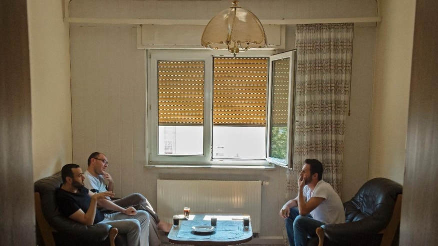 HOLD FOR RELEASE IN ADVANCE OF SEPT. 26 FOR USE WITH STORY BY HAMZA HENDAWI -In this photo taken Monday, Aug. 15, 2016, Mohammed al-Haj, right, talks with Mazen al-Ali, center, and Mohammed Zahlt, left, in their home in Saarbruecken, Germany. Al-Haj, a native of the city of Aleppo, Syria's one-time economic capital that now lies in ruins, came to the western German state of Saarland in September 2015 to benefit from its swift processing of migrants. (AP Photo/Jens Meyer)