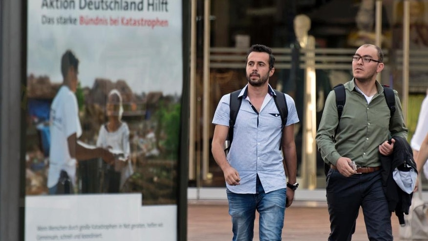 HOLD FOR RELEASE IN ADVANCE OF SEPT. 26 FOR USE WITH STORY BY HAMZA HENDAWI -In this photo taken Tuesday, Aug. 16, 2016,  Mohammed al-Haj, left, and Mazen al-Ali, right, walk besides a poster of the so-called 'Campaign Germany Helps' in Saarbruecken, Germany. Al-Haj, a native of the city of Aleppo, Syria's one-time economic capital that now lies in ruins, came to the western German state of Saarland in September 2015 to benefit from its swift processing of migrants. (AP Photo/Jens Meyer)