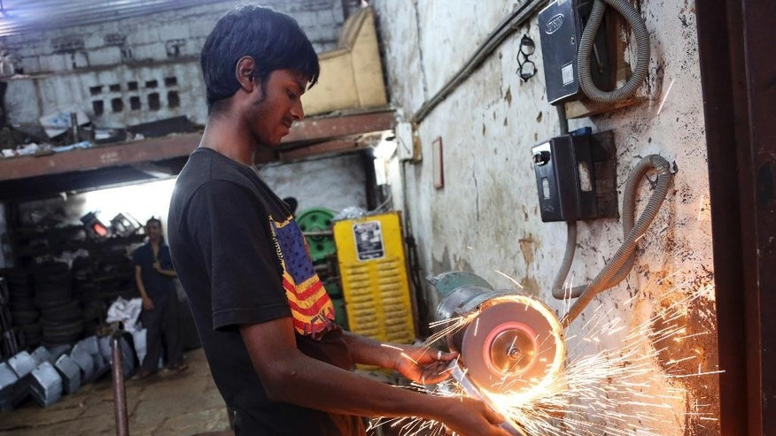 FILE - In this May 31, 2016 file photo, an Indian worker grinds metal to finish a part made for heavy vehicles at an industrial unit in Bangalore, India.  Developing economies in Asia are holding steady and will grow at the earlier forecast rate of 5.7 percent this year and next, buoyed by resilience in the region's two largest economies, China and India, the Asian Development Bank said Tuesday, Sept. 27, 2016. (AP Photo/Aijaz Rahi, File)