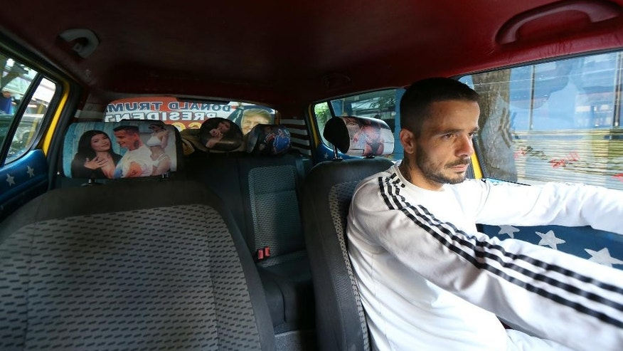 "Uljan Kolgjegja, 37, an Albanian taxi driver, drives his car with pictures of U.S. Republican candidate Donald Trump, in the Albanian capital, Tirana, Monday, Sept. 26, 2016. Uljan Kolgjegja said Monday he was prompted to decorate his taxi with pictures of the Republican candidate after Albania's Prime Minister Edi Rama said Trump could be ""a real threat to Albanian-American ties."" The move has attracted attention in the capital Tirana and Kolgjegja says he is earning more money than ever before in his 13 years as a taxi driver. (AP Photo/Hektor Pustina)"