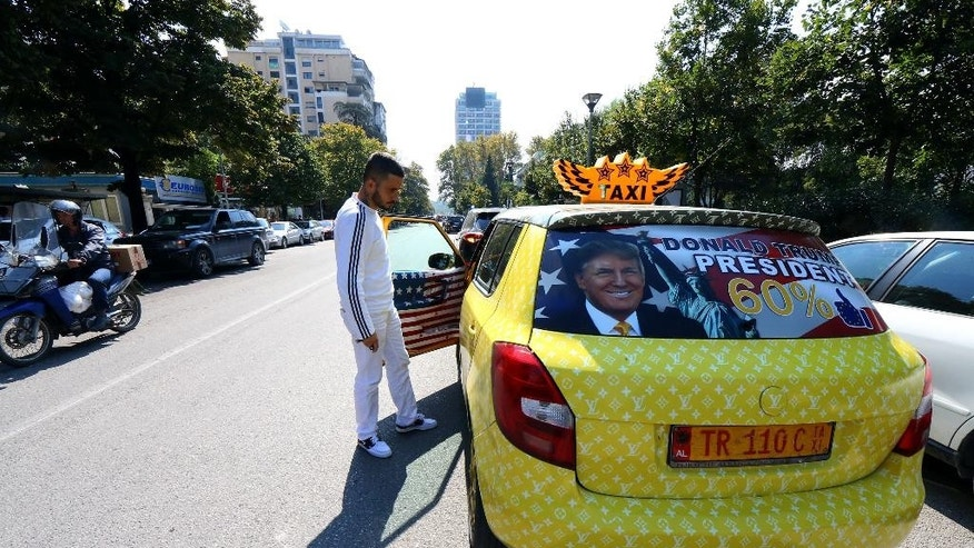 "Uljan Kolgjegja, 37, an Albanian taxi driver, shows his taxi  which he has covered with pictures of U.S. Republican candidate Donald Trump and U.S. flags, in the Albanian capital, Tirana, Monday, Sept. 26, 2016. Uljan Kolgjegja said Monday he was prompted to decorate his taxi with pictures of the Republican candidate after Albania's Prime Minister Edi Rama said Trump could be ""a real threat to Albanian-American ties."" The move has attracted attention in the capital Tirana and Kolgjegja says he is earning more money than ever before in his 13 years as a taxi driver. (AP Photo/Hektor Pustina)"