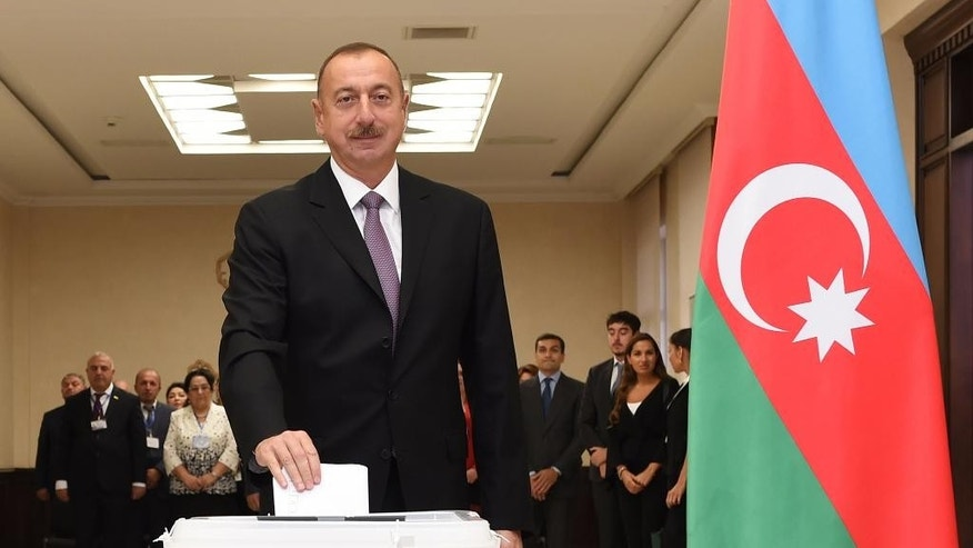 Azerbaijani President Ilham Aliyev casts his ballot at a polling station during a referendum in Baku, Azerbaijan on Monday, Sept. 26, 2016. The Monday vote is on proposals including raising the presidential term from five years to seven, granting the president the right to dissolve parliament and creating new appointed vice presidential posts. (AP Photo/ Vugar Amrullayev)